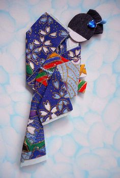 """NFT.  Hand-folded Japanese paper doll (""""ningyo"""") using yuzen washi for kimono and obi, viscose cord on obi, and nail art sticker and bud stick for hair décor.  Doll height: 8.9 cm"""