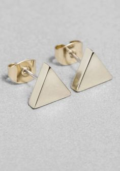 A pair of small, triangle-shaped stud earrings made from metal with a polished finish.