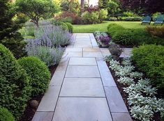 Boxwoods, lilacs and perennials line the walk while the gardens beyond beckon to the visitor.