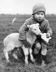 9th January 1937: Lamb being bottle fed by a very young farmer. (Photo by Fox Photos/Getty Images)