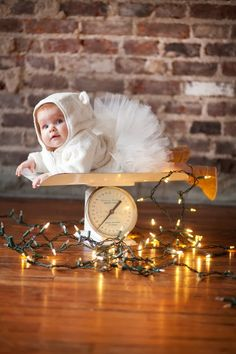 Oh. My. Goodness!!! Antique scale + Christmas lights + adorable baby girl in tutu, bear sweater & booties makes a sweet holiday photo. Photo by Krista Lee.