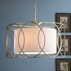 "A linen drum shade floats inside a hand-worked wrought iron frame of metallic circles. Specify Aged Silver metallic or Blackened Bronze finish. (16.5""Hx25""W)5x60 watts (candle base socket).Inner shade dimensions: 10""Hx18""W6' chain"