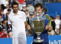 Andy Murray of Britain, right, looks at the trophy presented to him as Marin Cilic of Croatia looks on at the end of their Queen's Club grass court championships single final tennis match in London, Sunday, June 16, 2013. (AP Photo/Sang Tan)