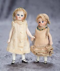 Two German all-bisque miniature dolls with swivel heads and cobalt blue eyes 500/800
