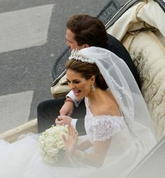 Princess Madeleine of Sweden and Christopher O'Neill sit in the royal horse carriage which carried them in a cortege around the city after their wedding at The Royal Palace Chapel on 08.06.13 in Stockholm, Sweden.