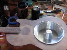 Homemade resonator guitar using cake tin and cheese greater for grill.