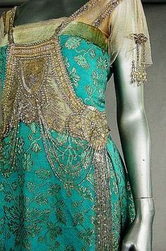 A turquoise and gold brocaded satin Evening Gown, ca. 1917, un-labelled, the bodice adorned with tasselled panel of silver bugle beads, tulle sleeves, above draped skirt with wide inner petersham waistband. https://musetouch.org/?cat=35