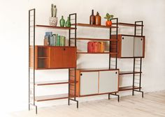 Beautiful freestanding three bay wall unit. Teak cabinets and shelves, two cabinets with grey/off white laminate doors suspended by black metal