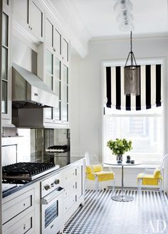 chic galley kitchen with black and white floors and cabana striped relaxed roman shade