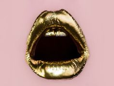 Golden lips isolated. Open sexy mouth with gold lipstick on pink background. Icon for women's female lips cosmetics. Sensual girl or woman with expensive luxury gold make-up. Golden teeth for party