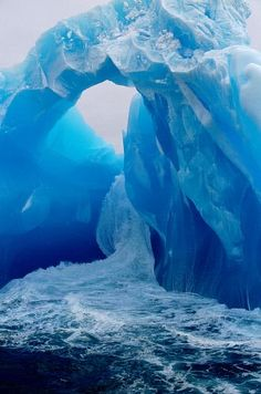 Waves surge round an ice arch on an ancient blue iceberg. Antarctica.