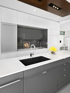 The high-gloss gray cabinets from Ikea set off the white and give this kitchen a nice visual landing place that white cabinets would not provide. This gray is about as achromatic as it comes.