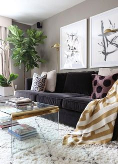 Love this glamorous living room with a charcoal gray velvet couch, potted fiddle leaf fig tree, lucite and gold coffee table, oversized watercolor abstract art prints, and white and black diamond pattern Moroccan shag rug.