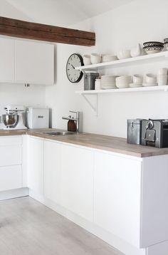 O relógio clássico faz o diferencial nessa cozinha clean.