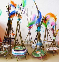 Mini woven teepees... made from sticks, cardboard, yarn, and feathers.
