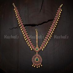 Designer maang tikka studded with synthetic ruby & green stones & plated with antique gold polish