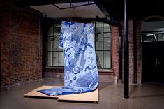 Semi Set Vertical Blue, jacquard tapestry (digital weave) in cotton and wool blend, installed on ​a plywood platform with nylon rope, clamps, plastic rod. 6m x 2m x 1mm. 2017   Semi Set Vertical Blue is a six meter long tapestry inspired by the infinite capacity of the internet. Like building a website, weaving a tapestry allows the designer freedom to continue an image or idea beyond the limits of a page. Building A Website, Plywood, Infinite, Surfboard, Wool Blend, Weave, Freedom, Platform, Tapestry