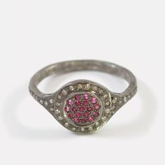 """This glamorous ring sparkles like a disco ball. Pavé set rubies are clustered in the center of a circular bezel, surrounded by a halo of pavé white diamonds. The 1/2"""" round bezel is gently curved to fit the finger. Pavé diamonds extend halfway around the band for even more sparkle. The sterling silver has been oxidized to a rich black, further accentuating the brilliance of the diamonds.Zoë Chicco lives and works in Los Angeles. Her designs are inspired by runway fashions, ..."""