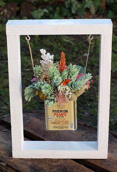 Flores secas, preservadas y artificiales (sólo las piñas verdes) en una taza que cuelga de una caja de frutas reciclada. Medidas: 19,5 x 30 cm (caja incluida en el centro) Se puede colgar en la pared a modo de cuadro o ponerlo sobre una superficie como en la foto. Las flores son duraderas y no requieren de ningún cuidado especial. Si te gusta este columpio pero quieres hacer algún cambio, escríbenos a tienda@floresenelcolumpio.com o ponlo en observaciones cuando hagas el pedido.