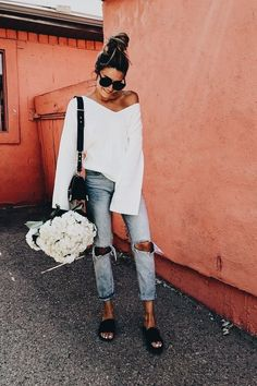 White off the shoulder top with distressed blue denim jeans.
