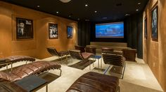 The home theater goes for old Hollywood luxury with gold walls and leather chairs. The three tiered room has leather recliners on the lowest tier and leather lounge chairs on the top two.