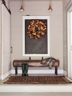 A gymnastics pommel horse, with its legs shortened, serves as a bench in a mudroom. The seasonal wreath hangs on a framed chalkboard.
