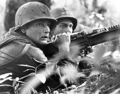 U.S. machine gunner Spc. 4 James R. Pointer, left, of Cedartown, Ga., and Pfc. Herald Spracklen of Effingham, Ill., peer from the brush of an overgrown rubber plantation near the Special Forces camp at Bu Dop during a half hour firefight, Dec. 5, 1967. Their company-size patrol avoided an ambush when a patrol dog alerted the unit to the presence of enemy forces. (AP Photo/Horst Faas)