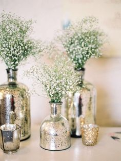 Small mercury glass budvases with baby's breath for highboys