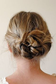 Braided knot | Split your hair down the middle like you're going to put it in pigtails. Braid each section back, away from your face. With each braided section in each hand, tie hair in a knot, and pin any loose ends into place with bobby pins.