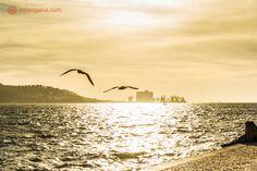 Pôr do sol na beira do rio Tejo, em Lisboa, no Padrão dos Descobrimentos, em Lisboa. Duas gaivotas voam no horizonte.