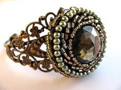 Sensational beaded rhinestone brass cuff bracelet handcrafted by DebsWhimsicalDesigns. For this embellished cuff, I rescued a broken vintage beaded brooch, set with a faux rhinestone, and gave it a new life by removing the pinback, gently sanding and adding to a brass filigree cuff bracelet. A marriage made in heaven!