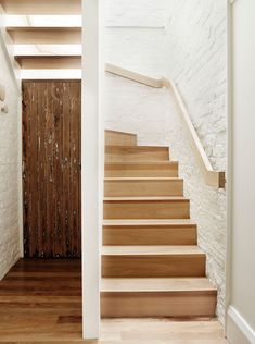 Simple light wood stairs and handrail as well as white painted brick lead you up to the second floor of this renovated home.