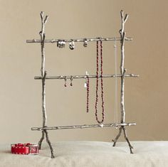 "JEWELRY ARBOR -- Bare branches blossom into a dramatic display with the addition of jewels. Sized to accommodate a prodigious collection, the arbor is brass with an antiqued silver patina. Lift the top two twigs to slip items on and off. 9-3/4""W x 6""D x 13-1/4""H."