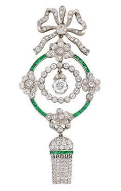An Edwardian diamond and emerald pendant set to the centre with an old brilliant-cut diamond estimated to weigh half a carat hanging to the centre of an old brilliant-cut diamond-set surround surrounded by four diamond-set flowers joined together by calibre-cut emerald-set links, with diamond-set bow top and diamond and calibre-cut emerald-set fringe at the bottom, circa 1910.