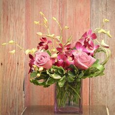 Pretty pink Roses and Orchids make a gorgeous arrangement.