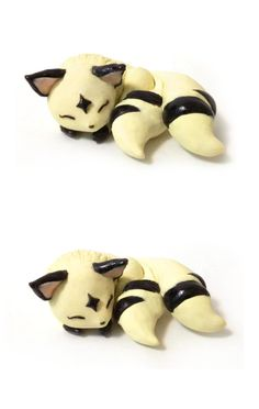 The kawaii Kirara from the anime show Inuyasha, is taking her beauty nap. She is made out of polymer clay and has glaze over the dark bands on her body.