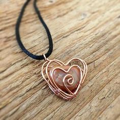"""This necklace features a copper, wire wrapped heart cage with handpicked agate inside. Copper heart is 20 gauge wire and woven together using 28 gauge copper wire. Charm measures 1"""" in length on a black satin cord that measures 22"""" in length. Satin cord is fastened with a silver"""