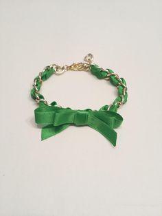 Pulsera en cadena dorada, con cinta de raso en verde, adornado con un lazo.