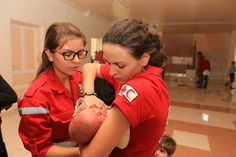 Two Syrian Arab Red Crescent volunteers carrying and checking a baby who has just arrived with his mother.