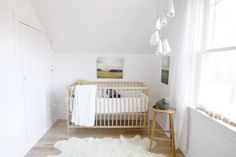 ": ""We kept the nursery minimal and light so we could add colour and update the space throughout Sebastian's childhood with accessories and artwork. The crib is IKEA. The blue bird pillow in the crib is handmade from salvaged wool by Three Bad Seeds. The artwork is an older landscape series from Walter Helena Photography. Sebastian loves anything shiny and sparkly – his favourite thing is to stare the disco ball above his changing table."