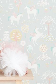 An enchanted garden with graceful unicorns with wings feature on this lovely wallpaper design perfect for a scandinavian style kids room.