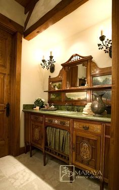 Guest bath. The owners had this beautiful antique vanity, altered. The cabinet was raised and extended side to side. New green marble top, sink and faucet.   Fauxed walls, handmade custom wrought iron fixtures and marble tile floors. There is an old oil painting on the back of the vanity.