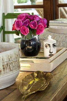 Details - Pink roses, hand-thrown pottery, a Fornasetti candle, and a 1970s brass accent piece on the coffee table
