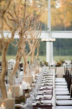 Tall branches in sand-filled vases are a perfect table centerpiece for a fall wedding.
