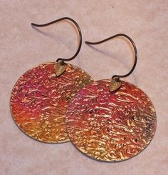 Round embossed earrings in watercolor shades of sunset with gold leaves.  Earrings are 1-1/4 inches in diameter and length and are made of sealed brass.  Ear wires are non-allergic brass and made without lead or nickel. 68311F    All content of this ArtFire store, including pictures, jewelry designs and art content © Catcophony Wearable Art