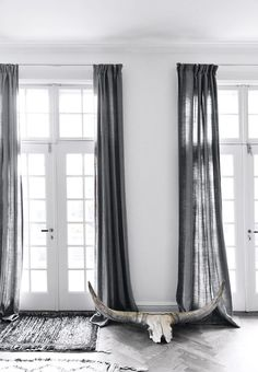 Curtains in linen in grey all the way down to the floor creates a restful feeling. Spice the room up with a grand antler - gives character and contrast.