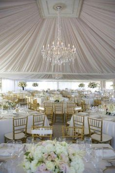 a large chandelier hanging from the center of a gorgeous fabric treated wedding reception in a ballroom with big windows. fabulous.