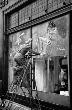 Decorating the hoardings on the shopfronts of Oxford Street, London 1940
