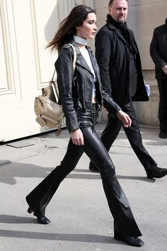 Bella Hadid wears black leather flared pants, a white choker top, black leather jacket, tan quilted backpack, and black square toe booties.