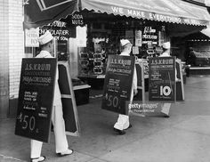 Three young men wear sandwich boards promoting the chocolates, candies, and soda fountain creations of J S Krum Chocolatier in front of the store at 2468 Grand Concourse, Bronx, New York City.